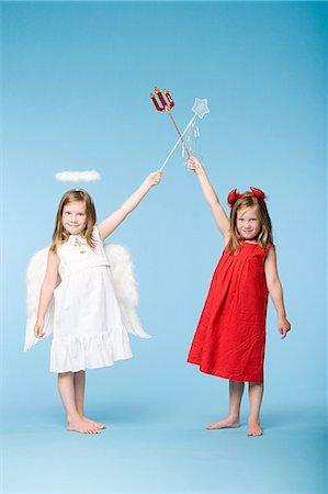 Twin girls dressed as an angel and devil Stock Photo - Premium Royalty-Free, Code: 6114-06608985