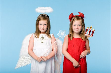 Twin girls dressed as an angel and devil Stock Photo - Premium Royalty-Free, Code: 6114-06608989
