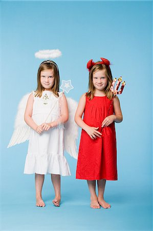 Twin girls dressed as an angel and devil Stock Photo - Premium Royalty-Free, Code: 6114-06608998