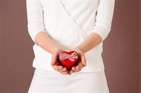 Woman holding heart shaped box Stock Photo - Premium Royalty-Free, Code: 6114-06609454