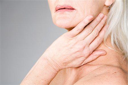Woman touching her neck Stock Photo - Premium Royalty-Free, Code: 6114-06609423