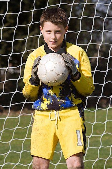 Goalkeeper holding football Stock Photo - Premium Royalty-Free, Image code: 6114-06610067