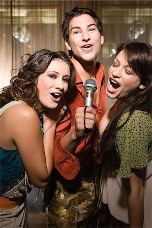 Friends doing karaoke Stock Photo - Premium Royalty-Free, Code: 6114-06610946
