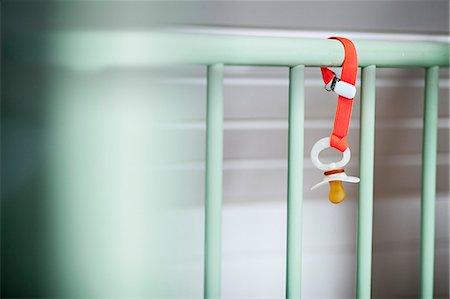 Baby's Pacifier Hanging On Baby Crib, Munich, Bavaria, Germany Stock Photo - Premium Royalty-Free, Code: 6115-06778541