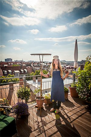 Young Woman On Balcony Holding Garden Rake, Munich, Bavaria, Germany, Europe Stock Photo - Premium Royalty-Free, Code: 6115-06778647