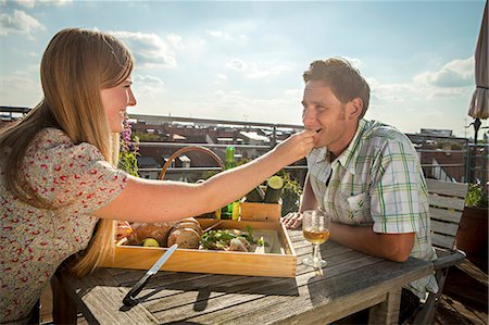 Woman Feeding Man On Balcony, Munich, Bavaria, Germany, Europe Stock Photo - Premium Royalty-Free, Code: 6115-06778663