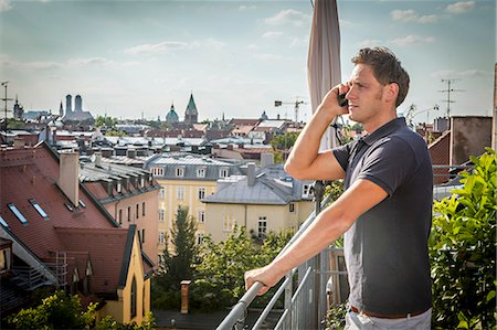 portrait looking away - Man On Balcony Using Mobile Phone, Munich, Bavaria, Germany, Europe Stock Photo - Premium Royalty-Free, Code: 6115-06778669