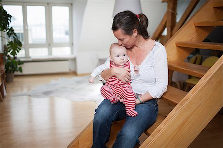 daughter kissing mother - Young mother with baby girl at home, Munich, Bavaria, Germany Stock Photo - Premium Royalty-Free, Code: 6115-06779105