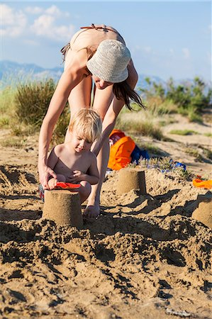 Croatia, Dalmatia, Mother And Son On Beach, Making Sand Cakes Stock Photo - Premium Royalty-Free, Code: 6115-06732891