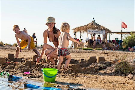 Croatia, Dalmatia, Mother With Sons On Beach, Background People Stock Photo - Premium Royalty-Free, Code: 6115-06732894