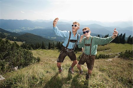 preteen dancing - Germany, Bavaria, Two boys in traditional clothing fooling around in mountains Stock Photo - Premium Royalty-Free, Code: 6115-06733167