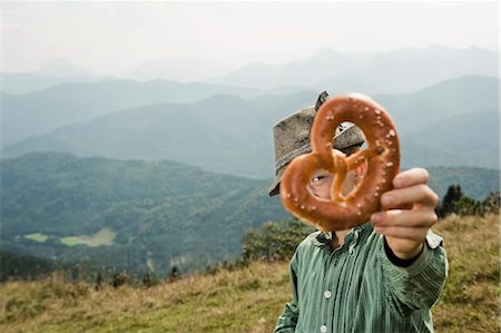 Germany, Bavaria, Boy in traditional clothing looks through a pretzel stick in mountains Stock Photo - Premium Royalty-Free, Code: 6115-06733169