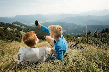 Germany, Bavaria, Two boys in mountains using a smart phone Stock Photo - Premium Royalty-Free, Code: 6115-06733173