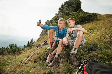 Germany, Bavaria, Two boys in mountains using a smart phone Stock Photo - Premium Royalty-Free, Code: 6115-06733174