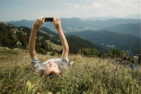Germany, Bavaria, Boy lying on back in mountains uses a smart phone Stock Photo - Premium Royalty-Free, Code: 6115-06733176