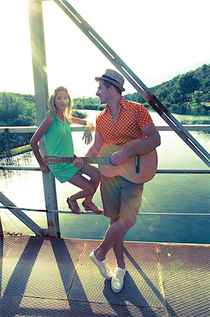 Croatia, Dalmatia, Young couple on a footbridge, man playing guitar Stock Photo - Premium Royalty-Free, Code: 6115-06733113