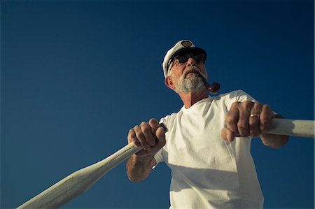 Croatia, Senior man with captain's hat steering sailboat Stock Photo - Premium Royalty-Free, Code: 6115-06733320
