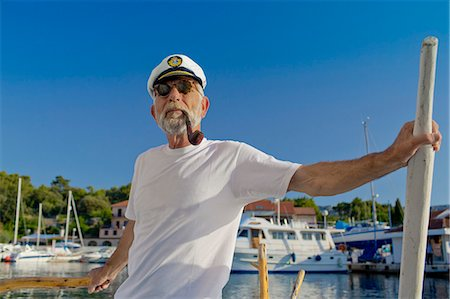 Croatia, Senior man with captain's hat on sailboat Stock Photo - Premium Royalty-Free, Code: 6115-06733328