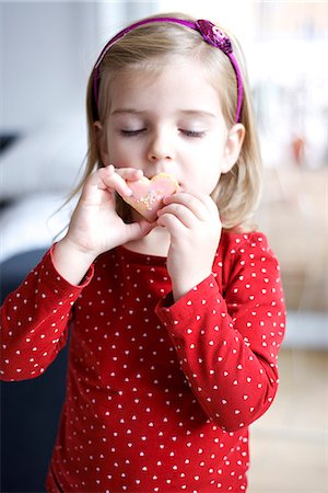 polka dot - Little girl tasting a cookie, eyes closed, Munich, Bavaria, Germany Stock Photo - Premium Royalty-Free, Code: 6115-06966972