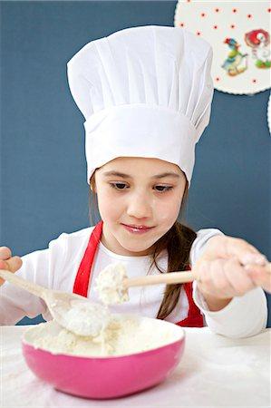 Little girl with chef's hat preparing dough, Munich, Bavaria, Germany Stock Photo - Premium Royalty-Free, Code: 6115-06966922