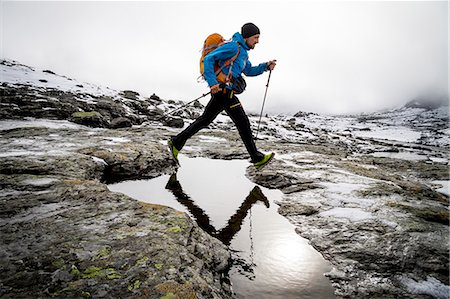 Hiker crossing mountain stream, Norway, Europe Stock Photo - Premium Royalty-Free, Code: 6115-07109785