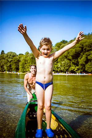 father son bath - Boy in bathing trunks in a canoe, arms raised, Bavaria, Germany Stock Photo - Premium Royalty-Free, Code: 6115-07282794