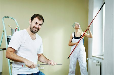 selecting - Woman painting the walls, man sits in the foreground, Munich, Bavaria, Germany Stock Photo - Premium Royalty-Free, Code: 6115-07282802