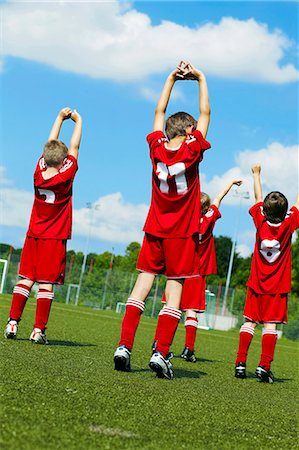 football team - Group of boys at soccer training, stretching, rear view, Munich, Bavaria, Germany Stock Photo - Premium Royalty-Free, Code: 6115-07539649