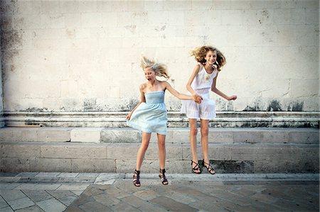 Two girls jumping in street, having fun, Zadar, Croatia Stock Photo - Premium Royalty-Free, Code: 6115-07539660