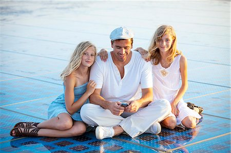 Father and two daughters sitting together on solar panels, Zadar, Croatia Stock Photo - Premium Royalty-Free, Code: 6115-07539667