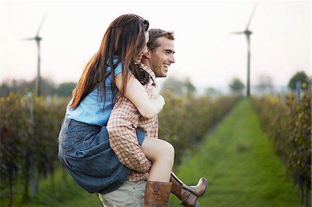 Man Giving Woman Piggyback Ride In Field, Croatia, Europe Stock Photo - Premium Royalty-Free, Code: 6115-07539604