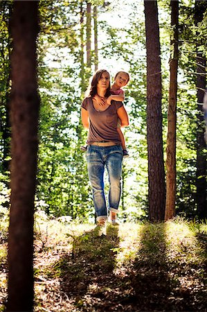 Mother carrying daughter piggyback through forest, Bavaria, Germany Stock Photo - Premium Royalty-Free, Code: 6115-07539804