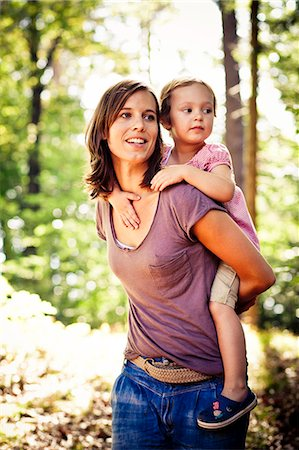 Mother carrying daughter piggyback in forest, Bavaria, Germany Stock Photo - Premium Royalty-Free, Code: 6115-07539805