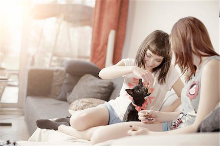 Two young women playing with pet dog Stock Photo - Premium Royalty-Free, Code: 6115-08066457