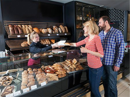 europe coffee shop - Female shop assistant in a bakery serving customers Stock Photo - Premium Royalty-Free, Code: 6115-08100516