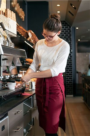 Waitress in coffee shop working at coffee machine Stock Photo - Premium Royalty-Free, Code: 6115-08100528