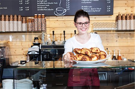 Waitress in coffee shop arranging croissants on counter Stock Photo - Premium Royalty-Free, Code: 6115-08100530