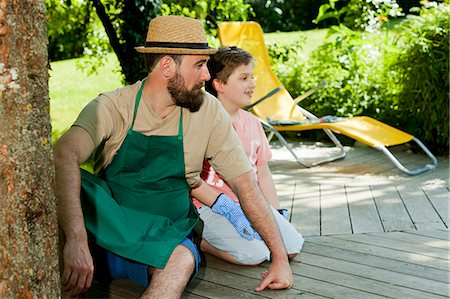 Father and son taking a break in the garden, Munich, Bavaria, Germany Stock Photo - Premium Royalty-Free, Code: 6115-08100607