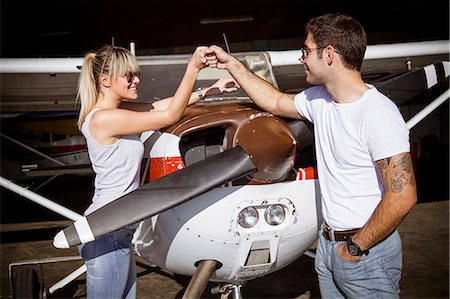 Young couple preparing for start in propeller airplane Stock Photo - Premium Royalty-Free, Code: 6115-08100853