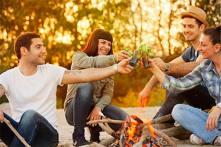 Group of friends by campfire toasting with beer, Osijek, Croatia Stock Photo - Premium Royalty-Free, Code: 6115-08101003