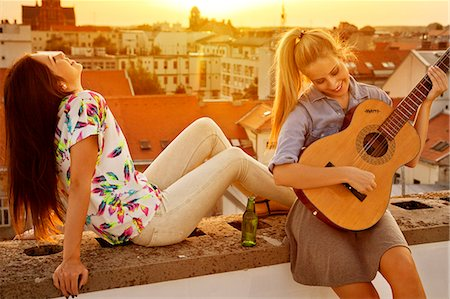 europe - Young woman with girlfriend playing guitar at rooftop party Stock Photo - Premium Royalty-Free, Code: 6115-08101146