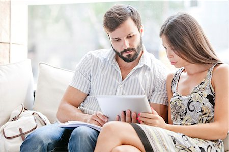 Young couple using digital laptop together Stock Photo - Premium Royalty-Free, Code: 6115-08101131