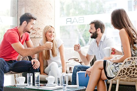 european cafe bar - Male students in cafe preparing for fist bump, girlfriends watching Stock Photo - Premium Royalty-Free, Code: 6115-08101135