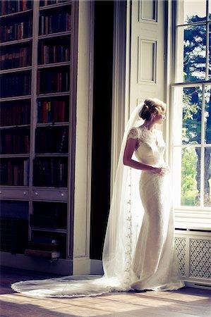 rich lifestyle - Wedding preparations, Bride in wedding dress by window, Dorset, England Stock Photo - Premium Royalty-Free, Code: 6115-08101208