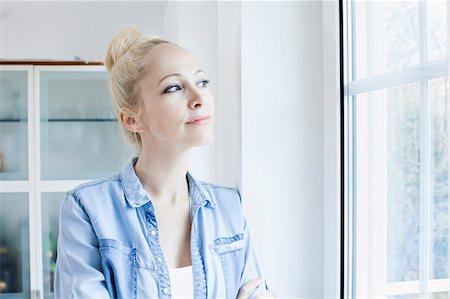 Blond woman looking through window Stock Photo - Premium Royalty-Free, Code: 6115-08104899