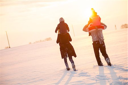 europe - Parents carrying children on shoulders in snowy landscape Stock Photo - Premium Royalty-Free, Code: 6115-08104983