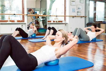 Group of women doing Pilates exercises Stock Photo - Premium Royalty-Free, Code: 6115-08105162