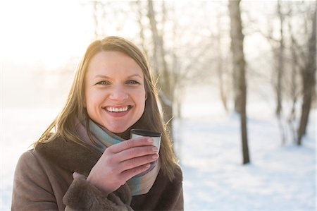 Young woman in warm clothing drinking hot tea outdoors Stock Photo - Premium Royalty-Free, Code: 6115-08105179