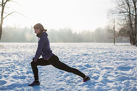 Young woman stretching in snow Stock Photo - Premium Royalty-Free, Code: 6115-08105184