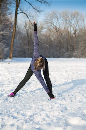 Young woman stretching in snow Stock Photo - Premium Royalty-Free, Code: 6115-08105186